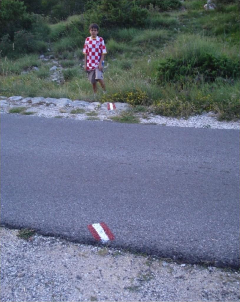 Notar a marcação do exato local onde a trilha deve atravessar a estrada (Parque Nacional de Lovcen, Montenegro).