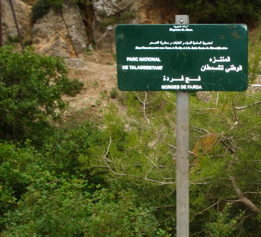 Placa de destino bilíngue, afixada em poste (Parque Nacional Talassantane, Marrocos)