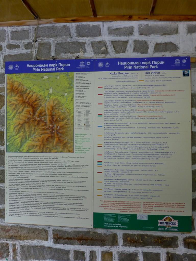 Placa base bilíngue no Parque Nacional Pirin (Bulgária). Notar o mapa e a descrição de cada trilha com a respectiva sinalização.
