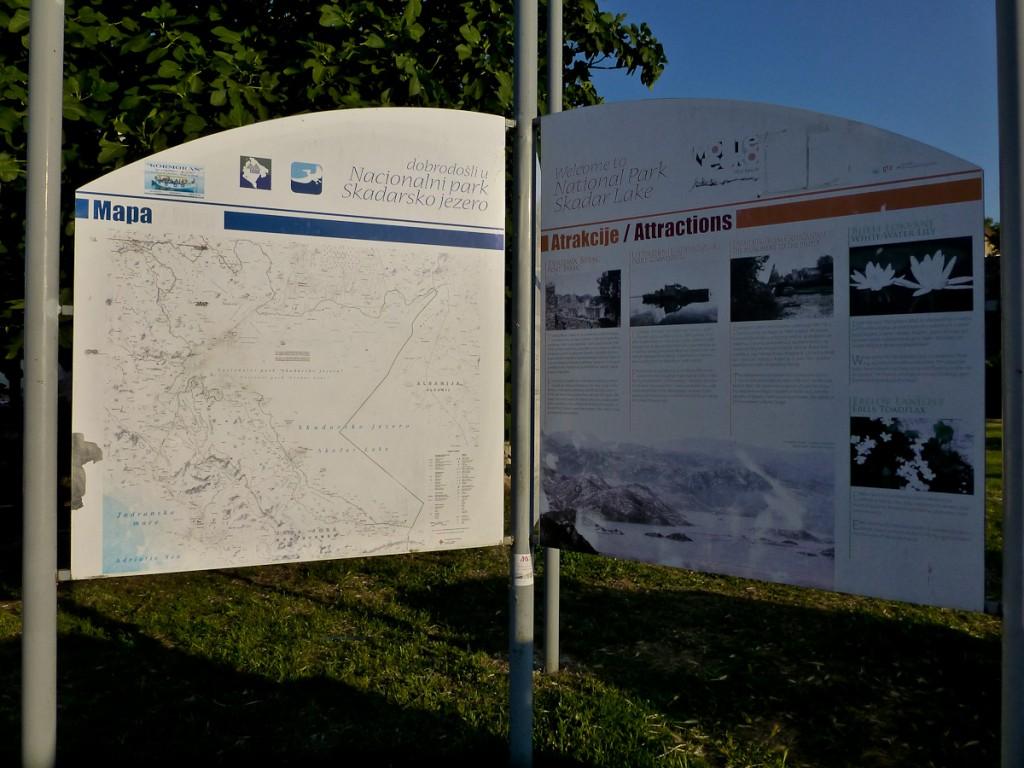 Placa base bilíngue com mapa de trilhas no Parque Nacional do Lago Skadar (Montenegro). Notar que cada atração é descrita por uma foto e APENAS dois parágrafos de texto.