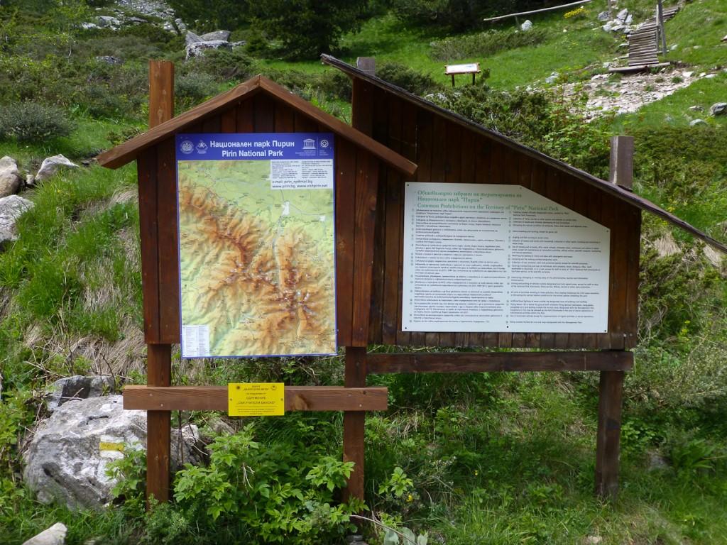 Placa base bilíngue no Parque Nacional Pirin (Bulgária). Notar os logotipos da unidade, do serviço de parques e de Patrimônio Mundial da Humanidade. Notar também o website do Serviço de Parques.