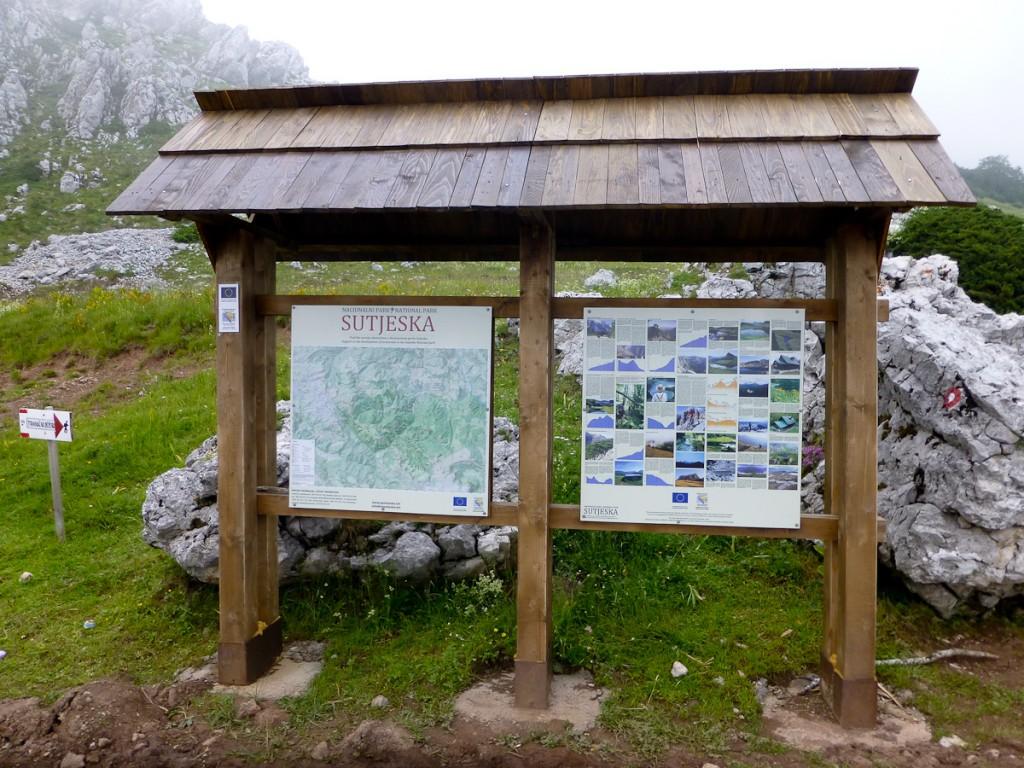 Placa base bilíngue com mapa de trilhas no Parque Nacional Sutjeska (Bósnia e Herzegovina). Notar que cada atração é descrita por uma foto e apenas dois parágrafos de texto.