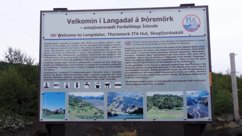Placa base bilíngue no Geoparque Katla, Islândia. Notar os ícones, os telefones de emergência e as coordenadas de GPS do local.