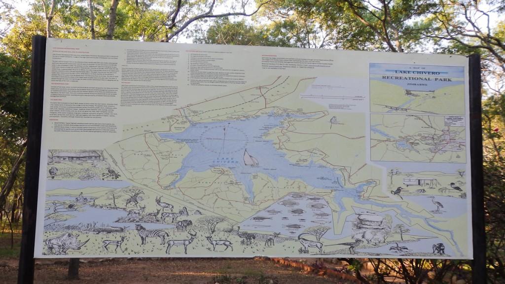 Placa base bilíngue com mapa de trilhas no Parque Recreativo do Lago Chivero, Zimbábue. Notar que cada atração é descrita por apenas dois parágrafos de texto.