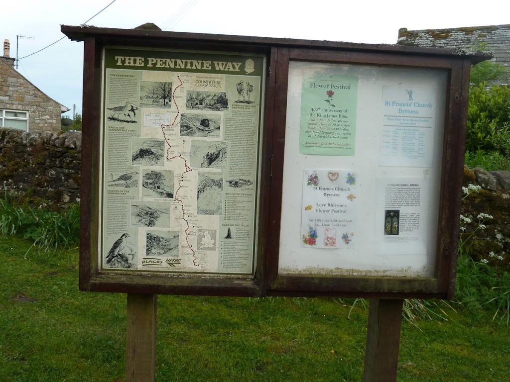Placa base na trilha de longo curso Pennine Way, no Parque Nacional Northumbeland (Inglaterra). Notar os logotipos de dois patrocinadores da placa em sua parte inferior.