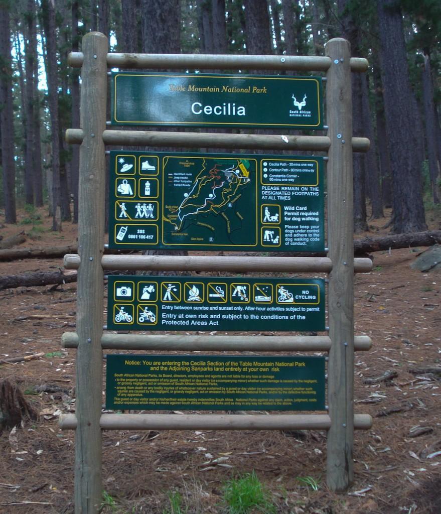Placa base com mapa de trilhas no Parque Nacional da Montanha da Mesa (África do Sul). Notar que quase toda a informação é passada por ícones. Notar também o termo de conhecimento de risco.