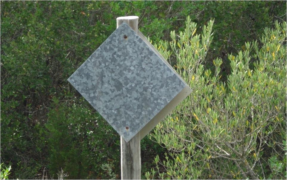 Placa colocada no sentido leste-oeste. Após dois anos, devido à incidência direta do sol, perdeu todas as cores (Parque Natural das Serras de Aire e Candeeiros, Portugal).