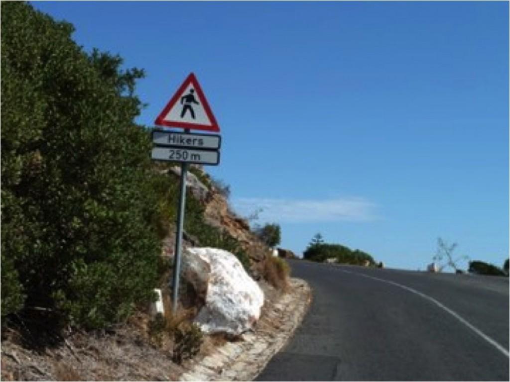 Exemplo de placa para alertar motoristas que à frente há uma trilha de montanhistas cruzando a via (Trilha de longo curso Hoerikwaggo, Parque Nacional da Montanha da Mesa, África do Sul).