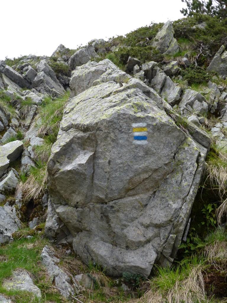 Sinalização direcional pintada de forma correta no espelho da pedra. Notar que há duas trilhas correndo sobre o mesmo leito (Parque Nacional Durmitor, em Montenegro)