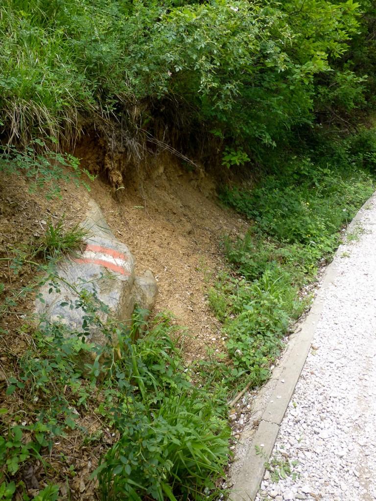 Sinalização direcional pintada no espelho de uma pedra, do lado esquerdo da trilha, pois não havia opção de pintura do lado direito (Parque Nacional das Montanhas de Sars – Kosovo).