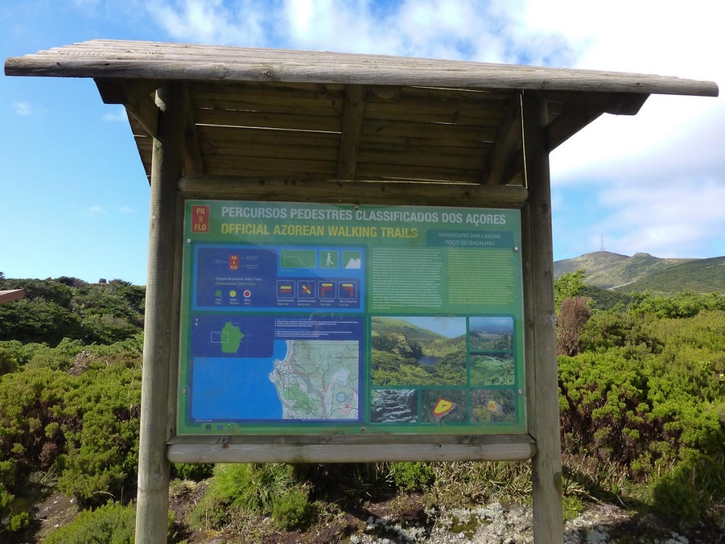 Placa-Base bilíngue com texto histórico, mapa de localização da trilha em relação à ilha, mapa detalhado da trilha, perfil altimétrico, explicação e fotografias da sinalização e fotografias de alguns atrativos (Parque Natural das Flores - Açores, Portugal).