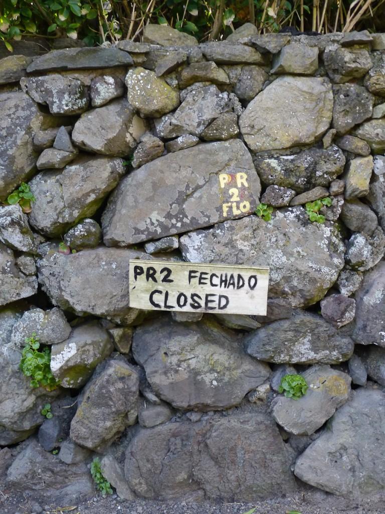 Trilha fechada por conta de deslizamento. Notar que a falta de recursos não impediu que um aviso fosse colocado com sinalização improvisada. Notar também que a sinalização direcional foi pintada sobre um muro/corpo estranho (Parque Natural das Flores, Açores - Portugal).