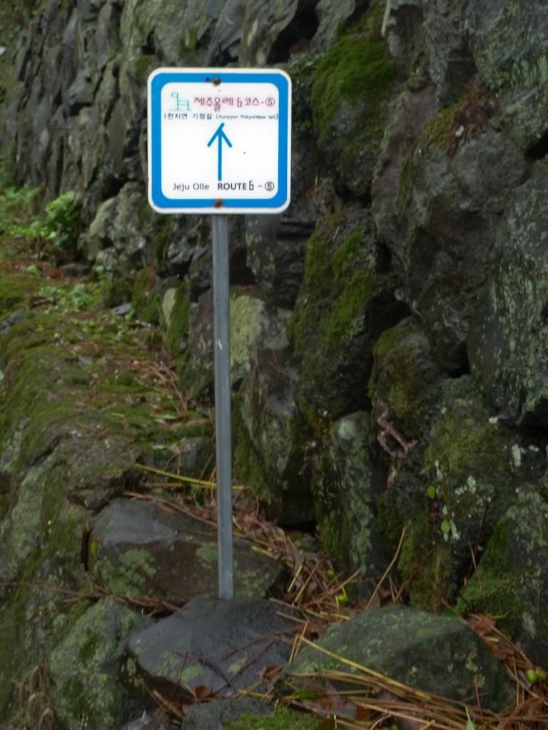 A sinalização direcional bilíngue da trilha de longo curso Jeju Olle, na Coreia do Sul, estava de pé.....