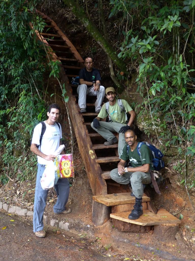 Notar que a sinalização direcional com a logomarca da Trilha Transcarioca foi pintada na lateral da escada. (Parque Nacional da Tijuca).