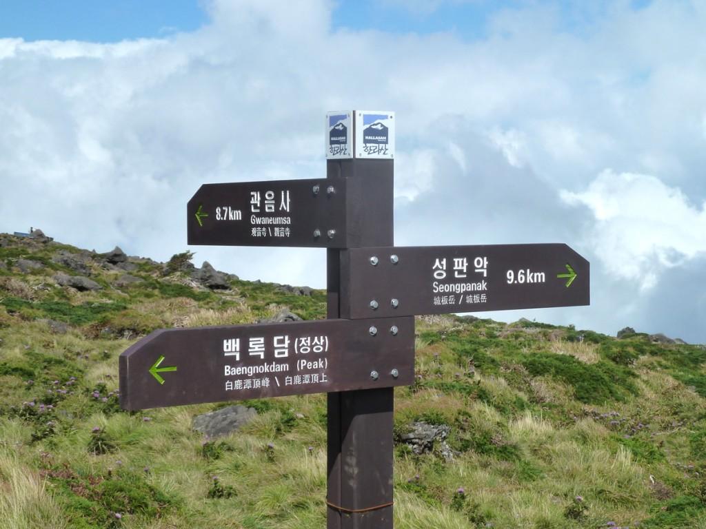 Exemplo de tabuleta colocada no meio da trilha, com sinalização direcional bilíngue, entalhada na madeira, e marcação da distância em quilômetros até o próximo destino (Parque Nacional Hallasam, Coréia do Sul).